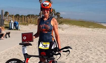 Triathlon woman on beach with bicycle