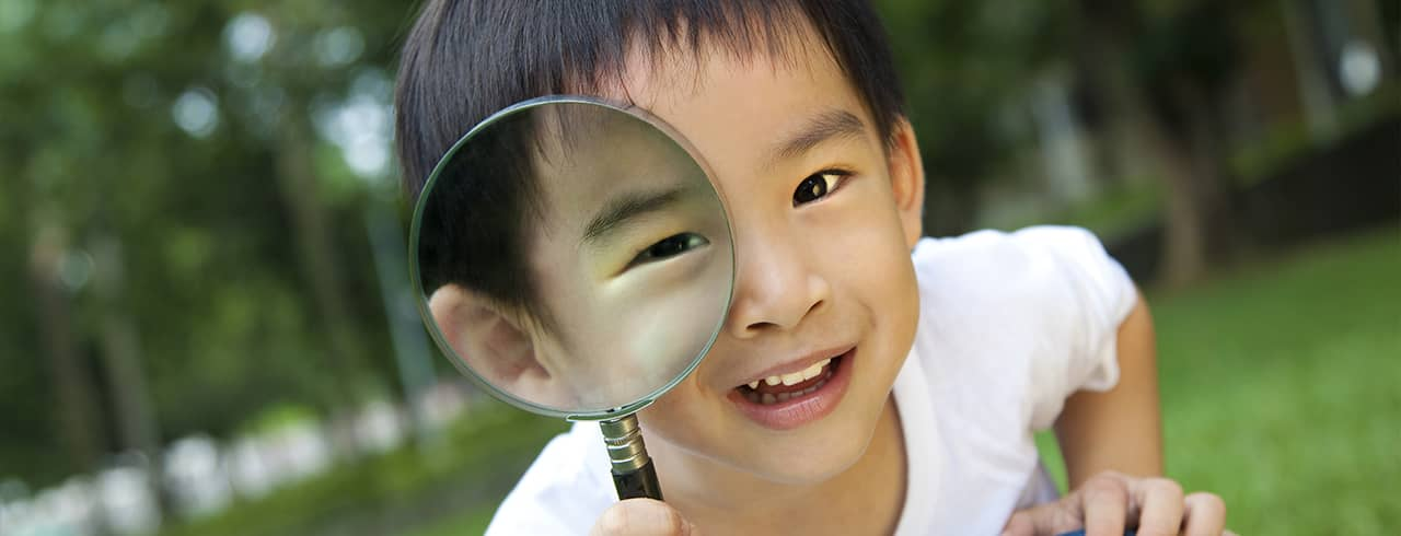 Little boy hold a magnifying glass