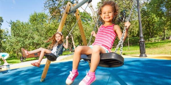 Two girls on playground swings
