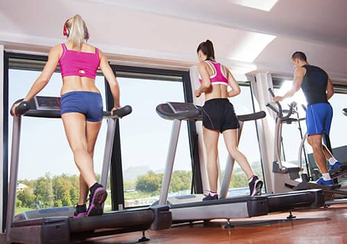 A row of women and a man walking on a treadmill
