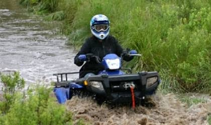 Woman driving ATV through water