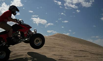 Riding ATV on sand dunes