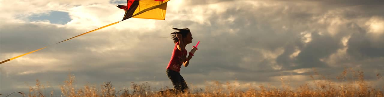 A child running in a field flying a kite