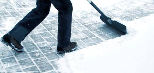 Person shoveling snow off walkway