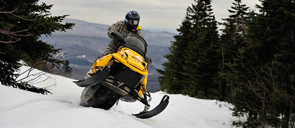 Man riding yellow snowmobile